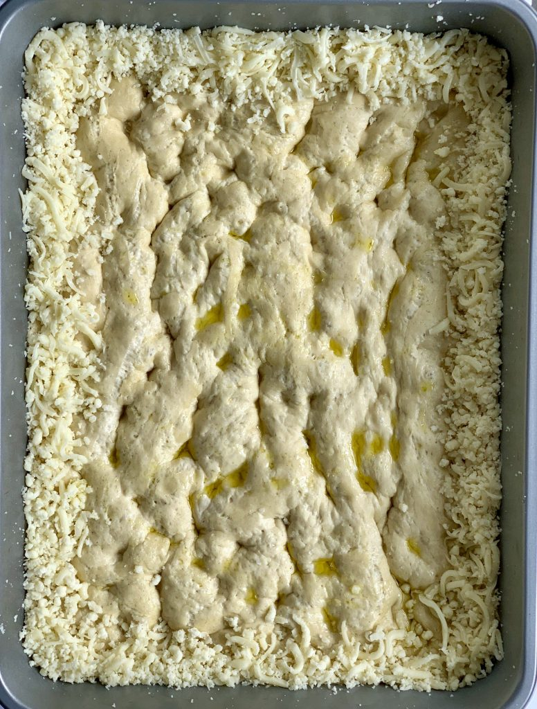 unbaked focaccia lined with cheese